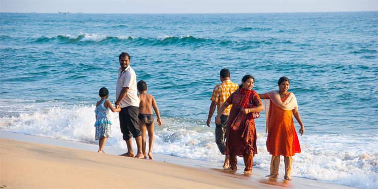 Indiase familie in de branding bij Varkala in India